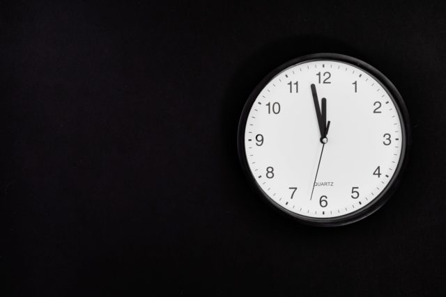 black round analog wall clock on black background