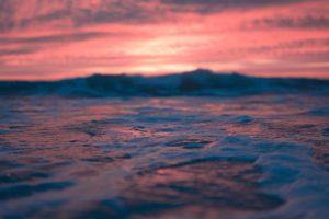 wavy ocean at bright sunset