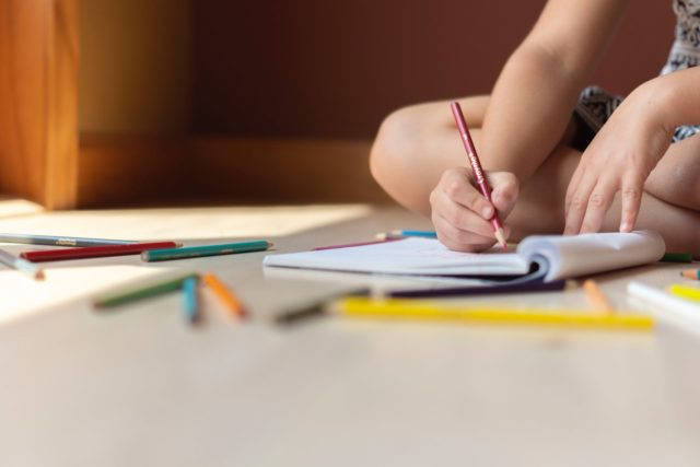 crop kid sitting on floor and writing in notebook
