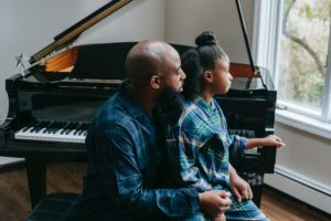 black father and daughter sitting near piano at home