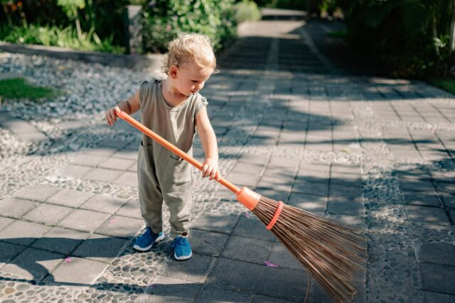 charming child sweeping path with broom in summer in sunlight