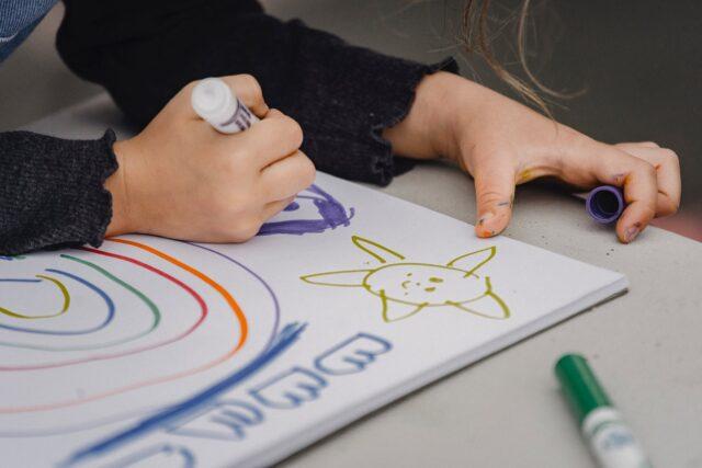 crop child drawing rainbow and sun