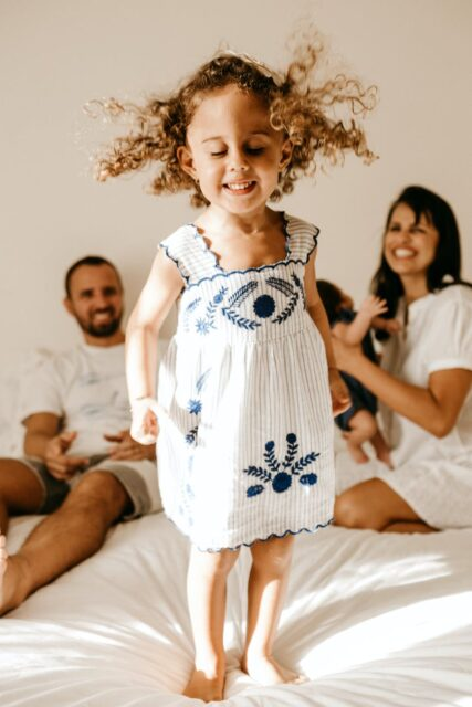 happy little kid having fun on bed with cheerful parents