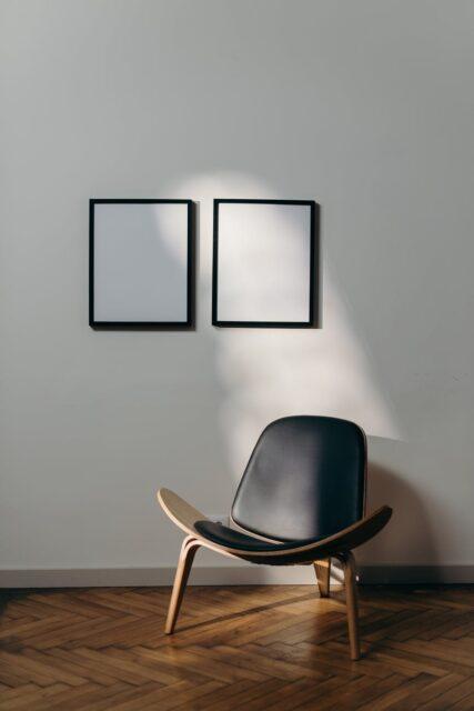 black wooden framed black padded armchair