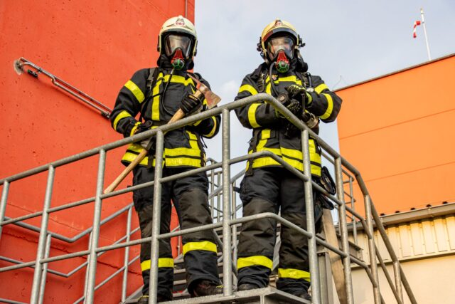 two firemen standing on stairs