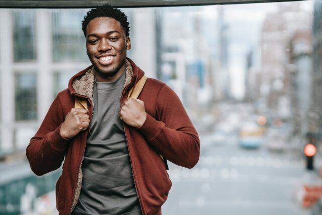 joyful black man near glass wall