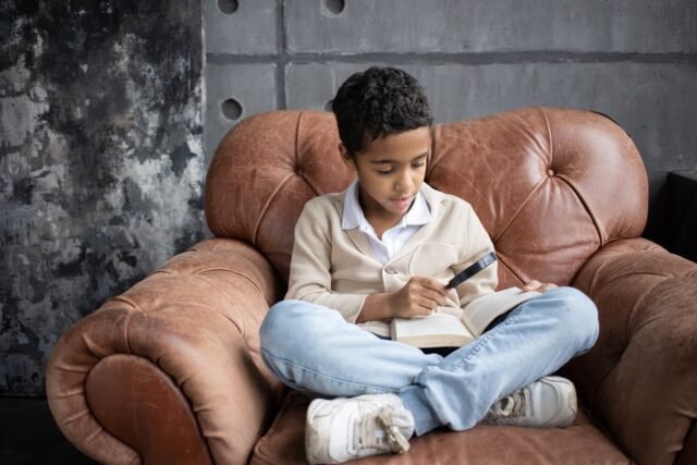 focused arabian schoolboy using magnifying glass to read interesting book