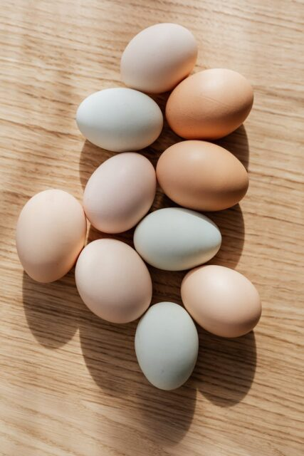 set of multicolored raw eggs on wooden table