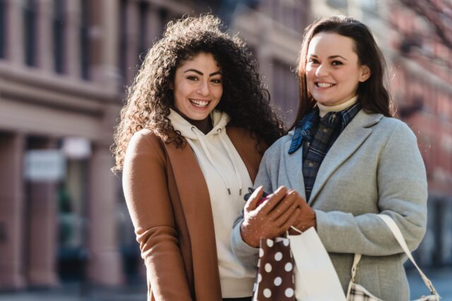 smiling female friends with gift packages in city street