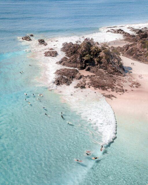 unrecognizable tourists swimming in ocean near rocky coast