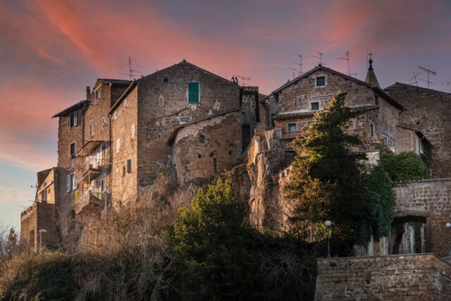 facades of aged stone houses located on hill under sunset sky