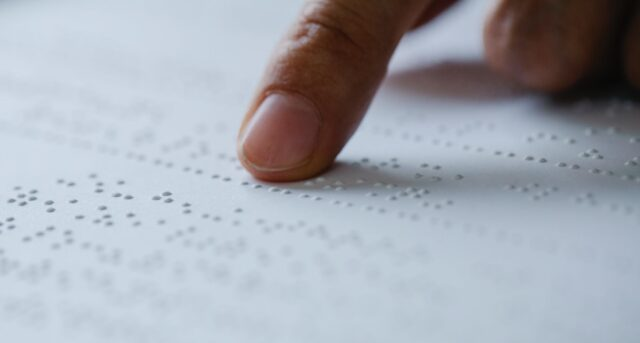 photo of person pointing on braille